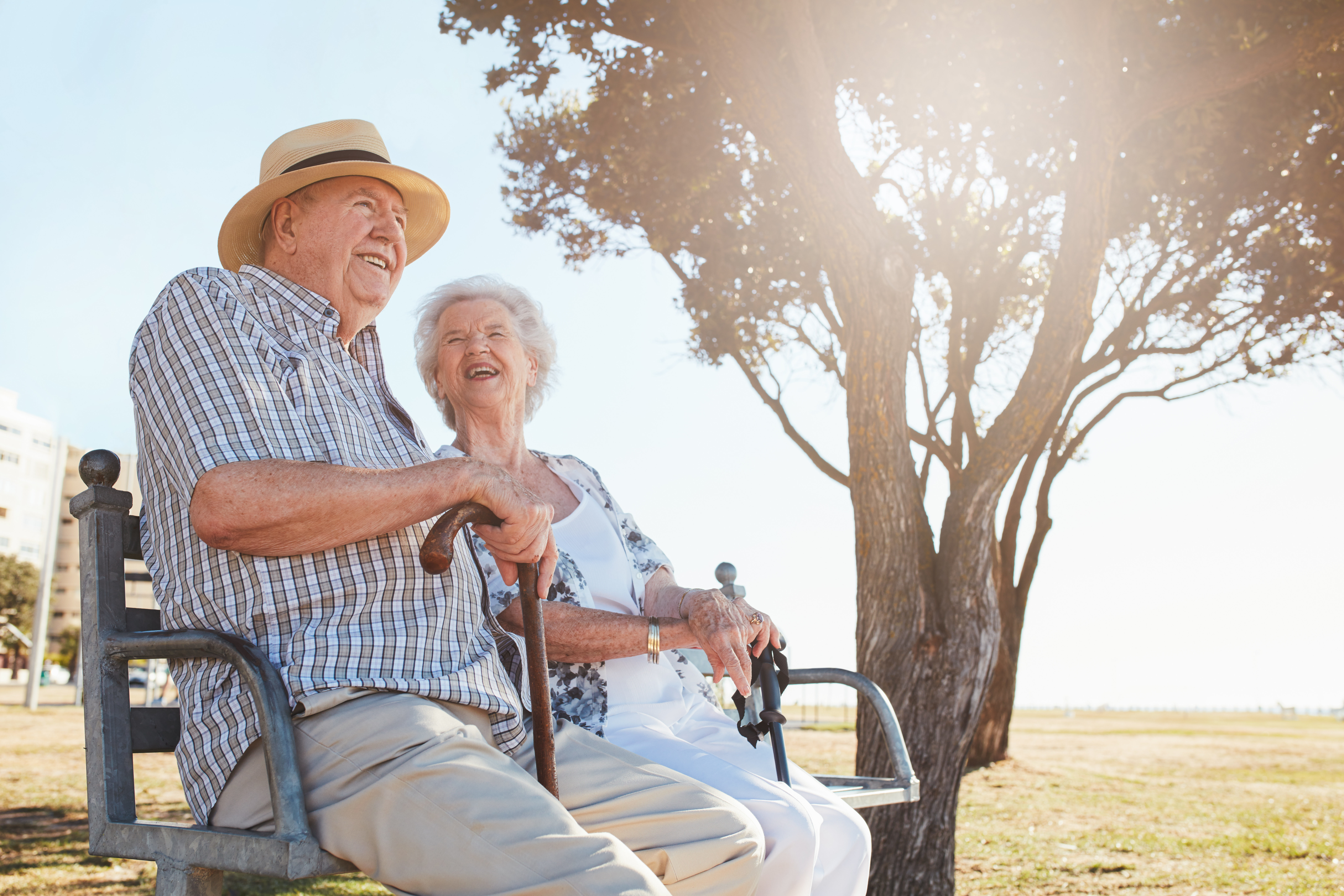 Elderly couple discuss medical alarm funding options in the sun.