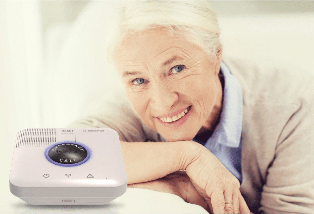 A woman with white hair poses next to a SECURELY in home medical alarm
